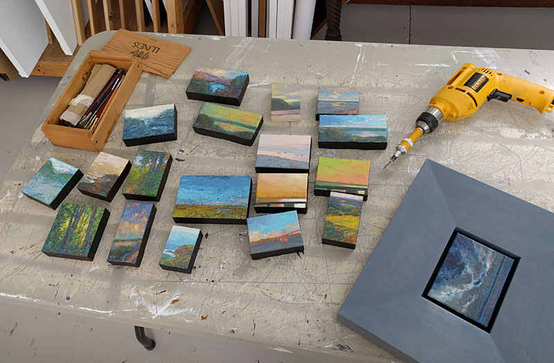 Tiny oil paintings on table.